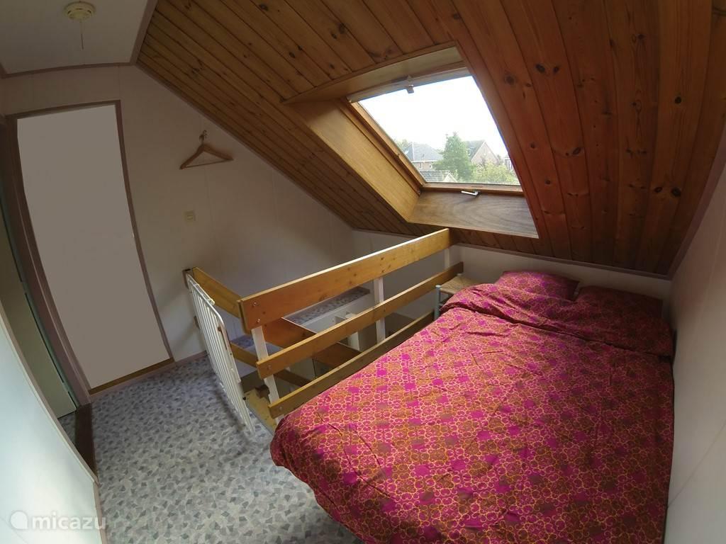 Twee persoons bed op de overloop boven.
