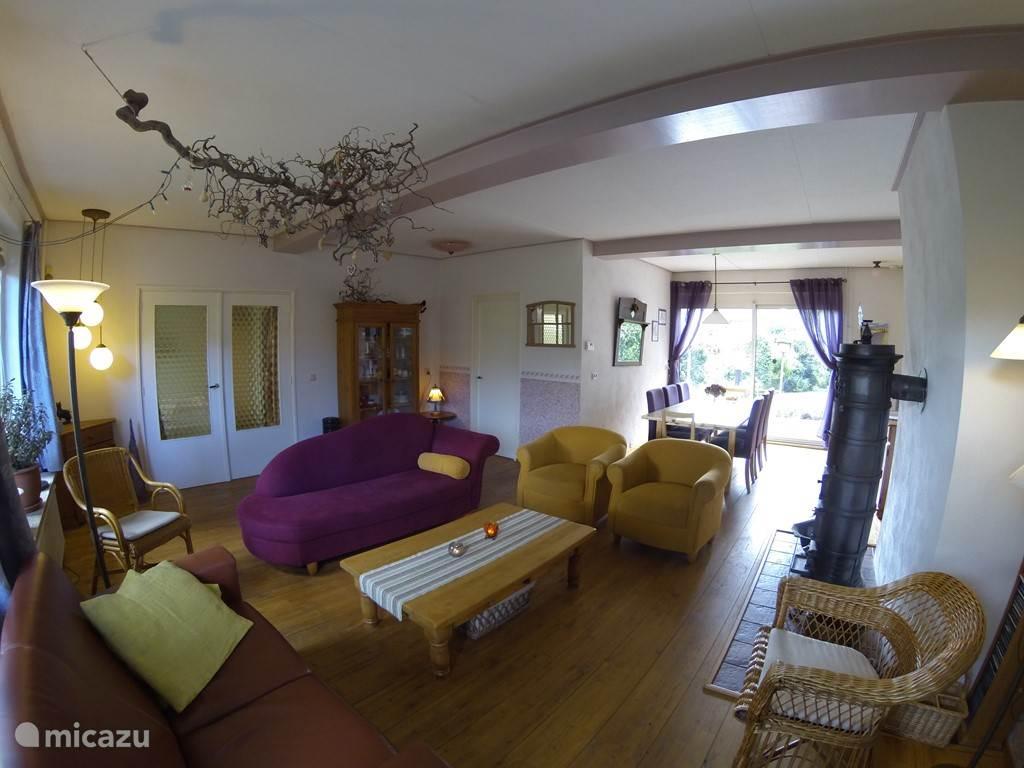 Overzicht van de huiskamer met schuifpui naar de tuin.