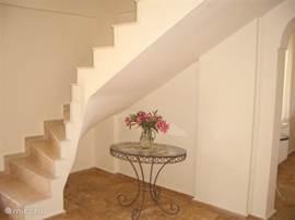 De stijlvolle trap naar boven, met het antieke tafeltje, op de kop getikt in een dorpje.