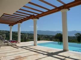 Het brede terras met aansluitend overloopzwembad. In het seizoen is de pergola bedekt met een zonnescherm, tegen de meest hevige zonnestralen, met voldoende mogelijkheid om de zon wél op te zoeken.