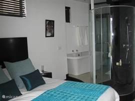 Voorste slaapkamer met open badkamer en toegang tot terrase