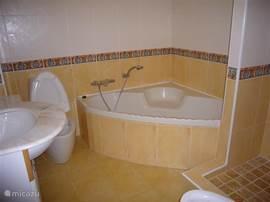 De tweede badkamer met groot hoekbad, aparte inloop douche, toilet, bidet en wastafel