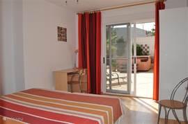 Tweepersoons slaapkamer met een schuifpui naar de tuin.
