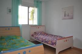 Kinderslaapkamer met twee bedden van 1.00 mtr breed. Er zijn leesboeken voor kinderen aanwezig.