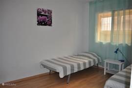 Slaapkamer met 2 een-persoons bedden.