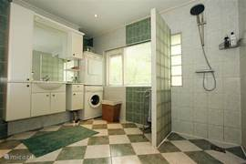 De ruime badkamer, voorzien van een grote 'regendouche', een wasmachine, een droger en een wasbak met kasten voor badlinnen, etc.