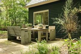 Voorzijde woning, met terras, meubels uit stijgerhout met kussens.
