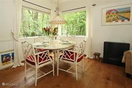 De eethoek met eettafel en vier stoelen met aan de rechterzijde de zwarte gaskachel.