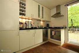 De open keuken, voorzien van alle gemakken met een direct aangrenzende deur naar de tuin aan de voorzijde.