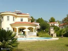 Luxe, vrijstaande Villa, gelegen in 1000 m2 eigen, ommuurde tuin met privé zwembad. Omringd door Oleanders, palmbomen en bloeiende struiken. Een zonneterras met grasveld bij het zwembad. Overdekte terrassen aan het huis, voor beschutting tegen de zon en om, samen met de airco het huis koel te houden