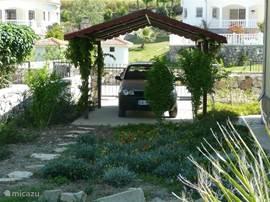 Een carport voor de auto. Het gehele terrein kan worden afgesloten met een hek.