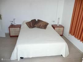 Een van de slaapkamers. Twee persoonsbed met nachtkastjes en leeslampjes.