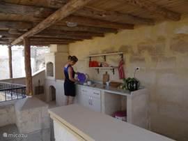 Op het dakterras is een tweede keuken met vaste stenen bbq, warm en koud water, een barretje en koelkastje. Voor koken moet je voorlopig nog even beneden zijn.