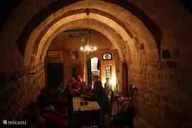 Op het overdekte deel van de binnenplaats kan je onder een kroonluchter heerlijk eten. Je kijkt hier zó de keuken in.