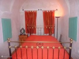 De slaapkamer beneden is vlakbij de badkamer en grenst aan de binnenplaats. Er is een ruime kleerkast in een nis.