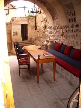 Op het overdekte deel van de binnenplaats is een loungeplek voor lange zomeravonden.