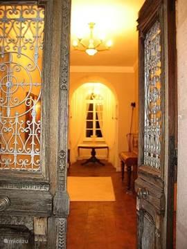 Doorkijk vanaf het bordes door de openstaande voordeur in de avond.