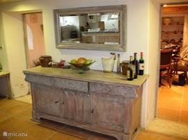 Dressoir in de keuken met rechts en links doorgang naar de eetkamer, 's avonds genomen.