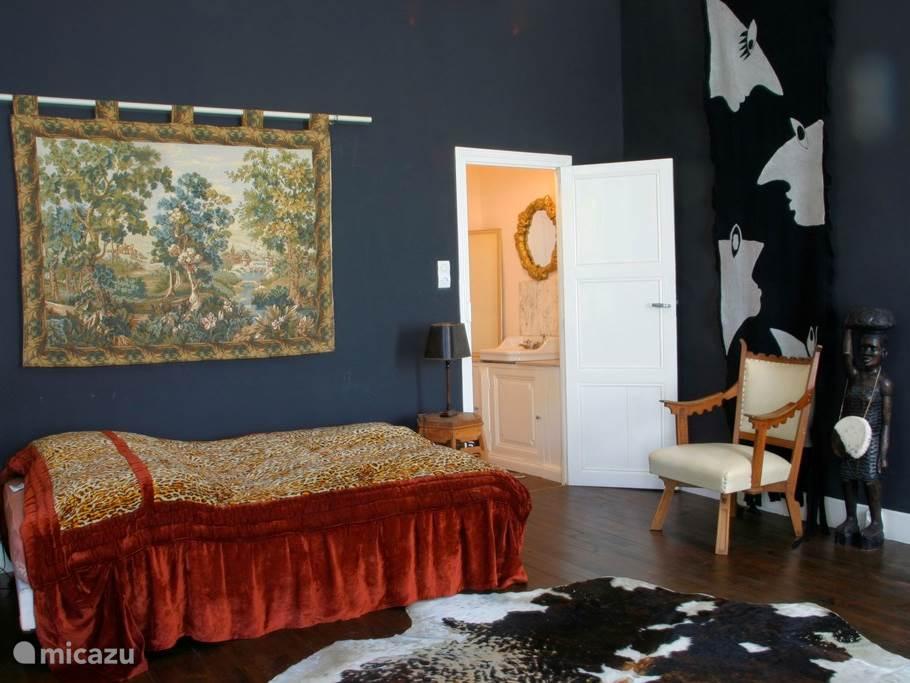Slaapkamer met tussenruimte met wastafel.
