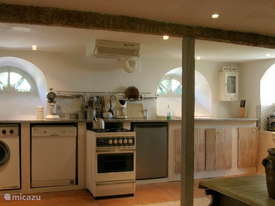 De ruime keuken met wasmachine, vaatwasser, gasfornuis en koelkast.
