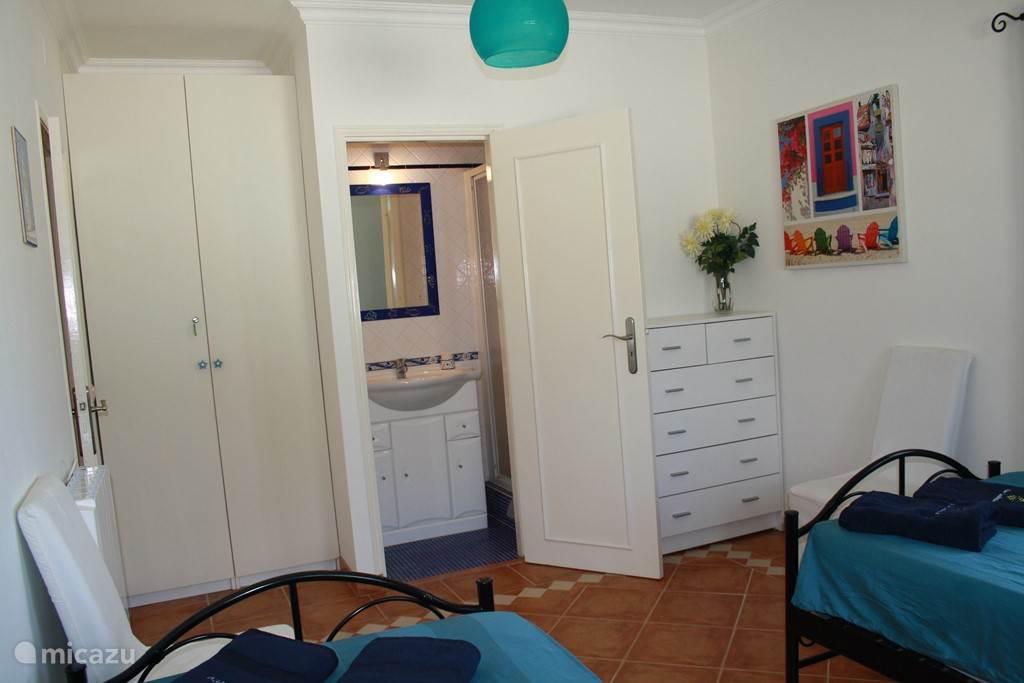 Douche-kamer en-suite, begane grond. Douche en vaste wastafel (grenst aan kamer met twee aparte bedden)
