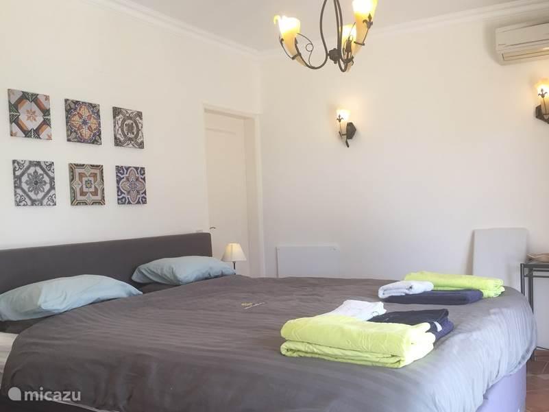 Tweepersoons master bedroom op de 1e verdieping (bed: luxe boxspring afm. 220x180), met eigen badkamer (en-suite) met luxe inloopdouche. Airco en verwarming. Terrasdeuren naar riant lounge terras met zeezicht.