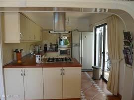 Keuken met roestvrijstalen inbouwapparatuur (afwasmachine, oven, magnetron). Amerikaanse koelkast. Alle keukenbenodigdheden. Schuifpui aan zijterras met zitje voor een ontbijtje in de vroege ochtendzon.