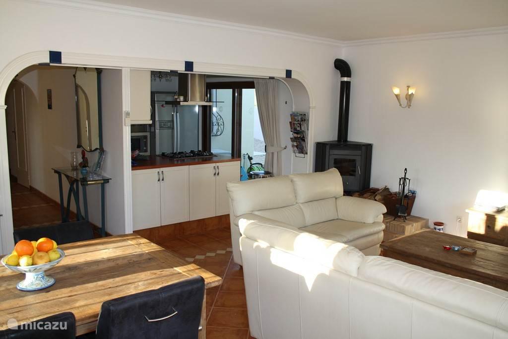 De woonkamer heeft een heerlijke eetkamertafel voor 6 personen met uitzicht op de tuin en zwembad, open keuken en open haard.