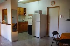 Keuken met grote amerikaanse koelkast, magnetron, 4-pits gasfornuis, koffiezet apparaat en broodrooster.