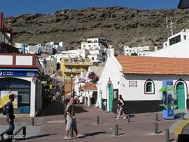 Blik op het huisje op de berg, vanuit het dorpje met op de voorgrond het kerkje van Puerto de Mogan.