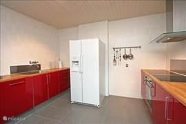 Keuken begane grond met grote Amerikaanse vrie-/koelkast, dubbele keramische kookplaat, hetelucht-oven en vaatwasser, waar je heerlijk voor z'n allen kunt koken!