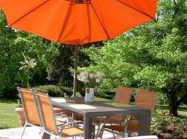 Onder de parasol genieten aan de eettafel. Uw gastvrouw en gastheer zorgen voor een fles wijn.