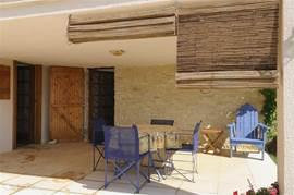 Overdekt beneden terras met tafel en 4 stoelen.