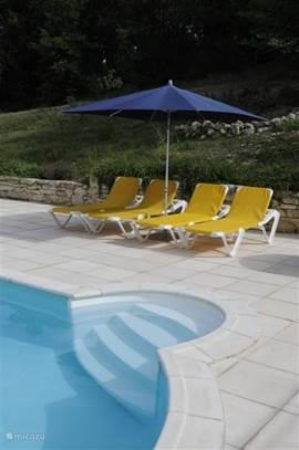 Ligstoelen en parasol bij het zwembad.