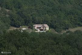 Foto van het huis vanaf de overzijde van het dal.