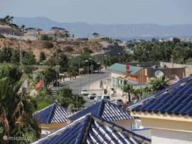 Vanaf dakterras zicht op golfbaan met dus veel groen en palmen, commerciële centrum (2 min lopen) en bergen....
