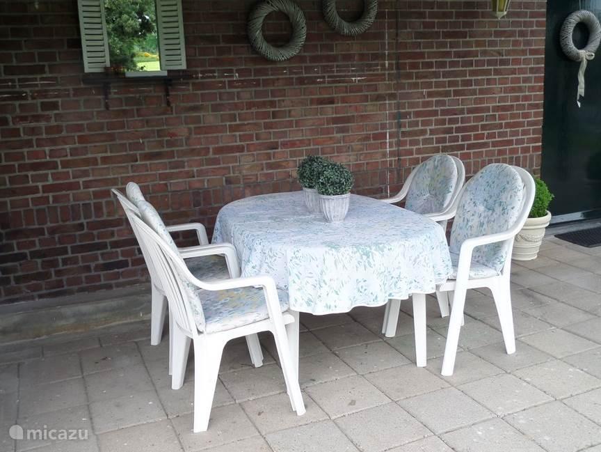 Overdekt terras, met tafel en 6 stoelen.