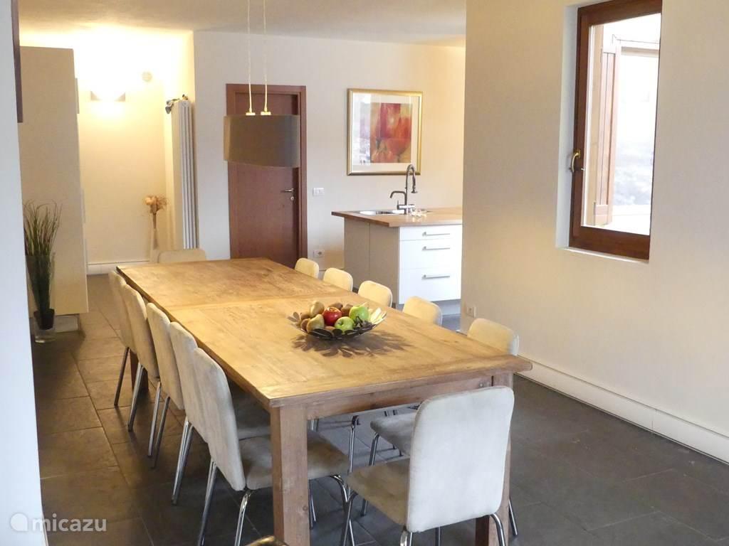 Lange tafel vanuit de woonkamer met zicht op keuken