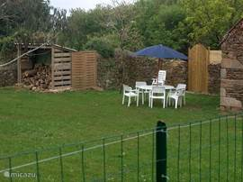 Tuin achter het huis met het brandhout voor de kachel en een stenen barbeque.