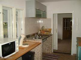 fully equipped kitchen with refrigerator, four burner stove, microwave, Senseo coffee maker and small.