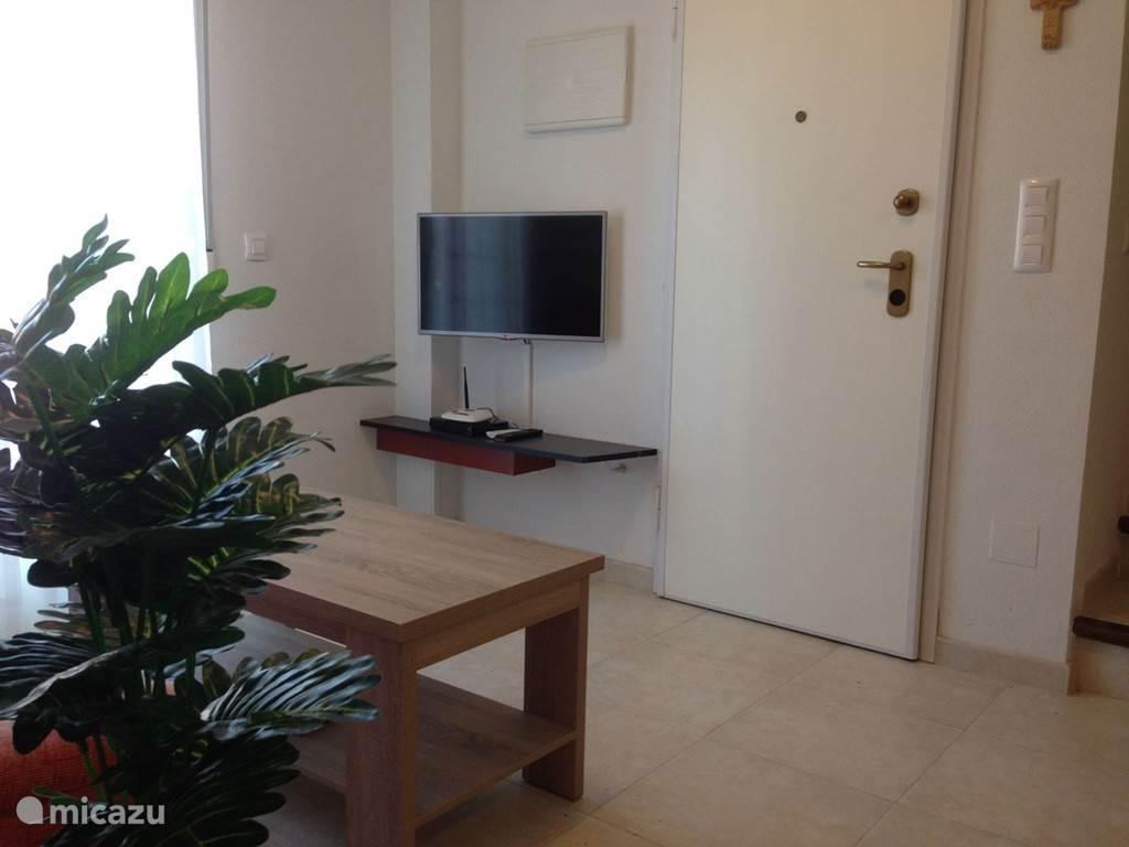 De zitbank met salontafel en de Flatscreen TV aan de muur bevestigd. Nederlandse TV kanalen en Wi-Fi is aanwezig.
