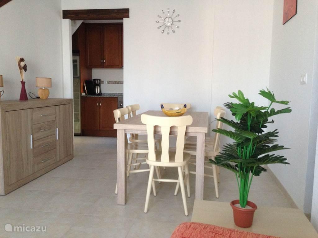 De woonkamer aan de kant van de keuken met een eettafel voor 6 personen