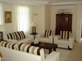 De volledig ingerichte woonkamer met bankstel, fauteuils en eetkamertafel.