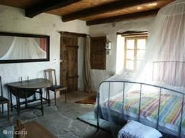 Slaapkamer1 Ruime slaap kamer met 2 persoonsbed en zitje bij de houtkachel. Grenst direct aan de binnenplaats en heeft uitzicht op het terras en de heuvels.