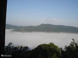 Het uitzicht zoals het in het najaar kan zijn. Het huis boven de wolken.