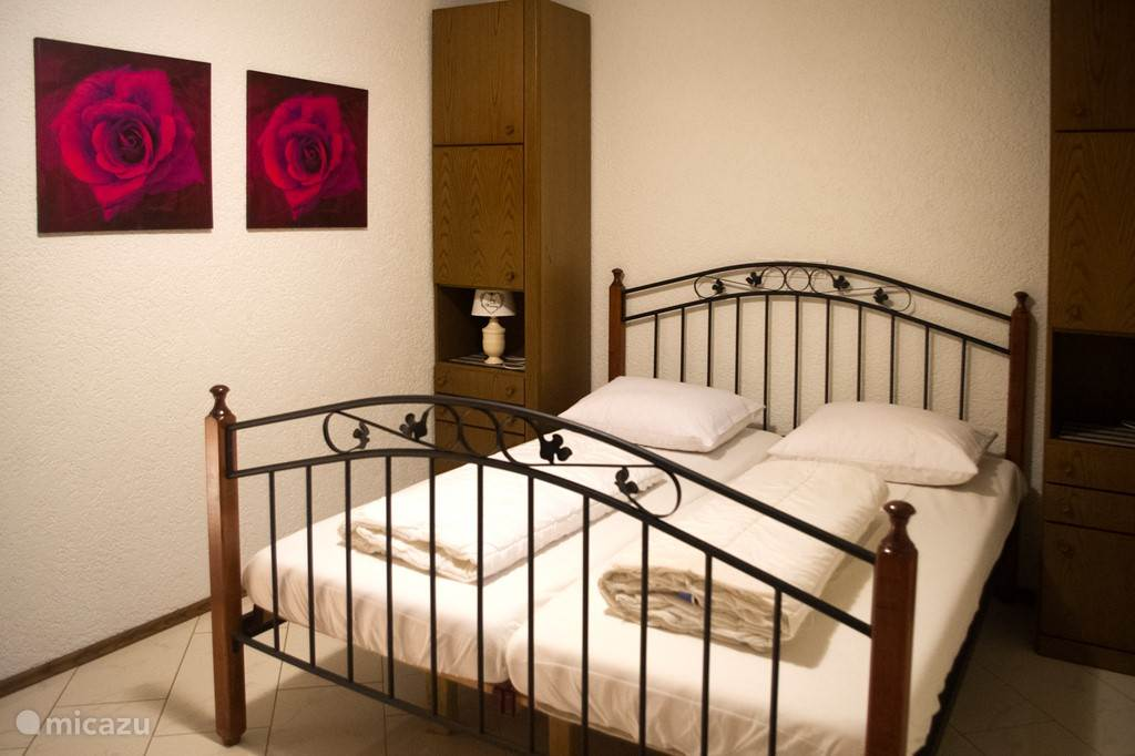 Slaapkamer achterzijde met tweepersoonsbed en stapelbed, naast de badkamer.