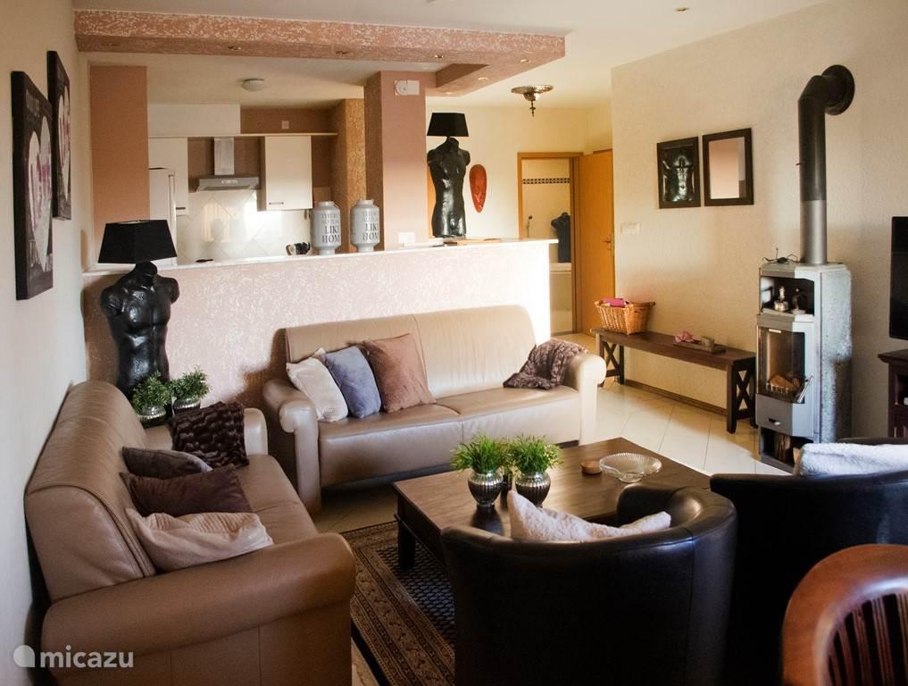 Compleet ingerichte woonkamer met heerlijk zittende bank en fauteuils.