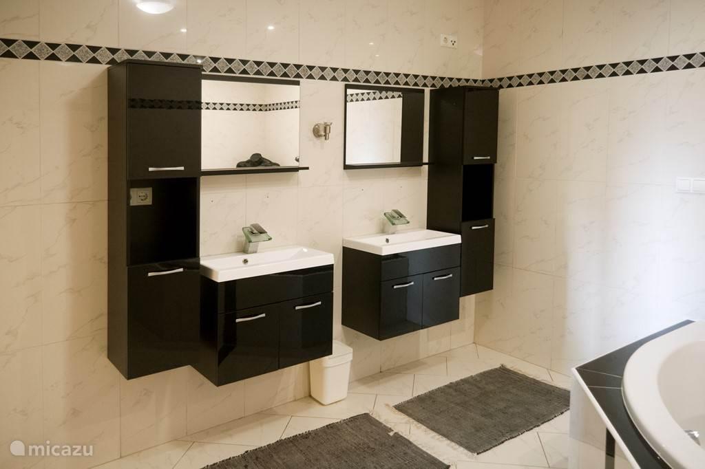 Riante badkamer voorzien van tweepersoons ligbad, dubbele wastafel, separate douche en tweede toilet.