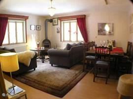 De ruime woonkamer in het appartement geschikt voor 4-6 personen. 1ste verd. Of een combinatie met de 2e verdieping voor 10 personen.Met comfortabele banken, een grote eettafel en een gezellige houtkachel. Hier voelt u zich direkt thuis.