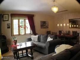 De ruime woonkamer met comfortabele banken en gezellige houtkachel.